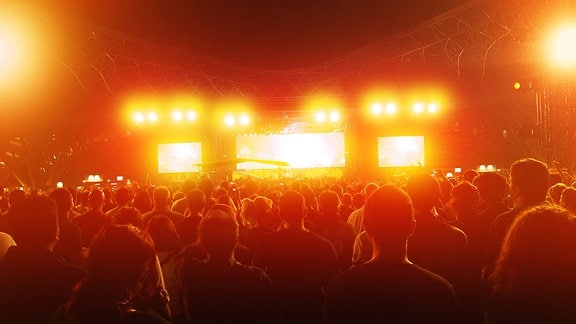 Menschen stehen vor einer Bühne und betrachten eine beeindruckende Lichtshow.