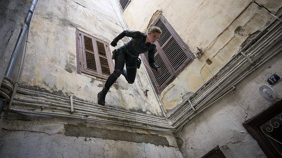 Filmszene - Eine Frau läuft an Seilen eine Hauswand hinab.