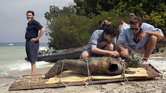 Männer am Strand. Rechts bücken sich zwei Männer, ein junger und ein älterer über eine antike Skulptur, die auf eine Bare festgezurrt ist. Rechts steht ein dicker Mann und schaut in die Kamera. Von rechts nach links: Mr. Perlman (Michael Stuhlbarg), Elio (Timothée Chalamet) und Oliver (Armie Hammer)