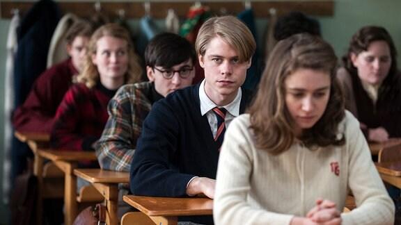 Bedrückte Schulkasse sitzt auf Stühlen. In der Mitte blickt ein junge, blonder Schüler trotzig in die Kamera