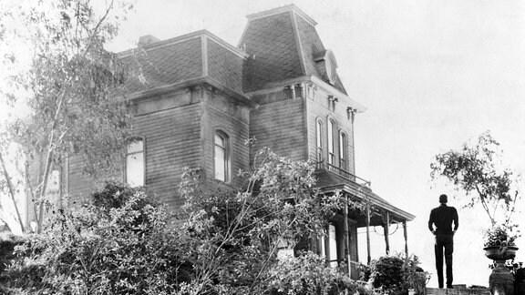 Filmszene aus Psycho in Schwarzweiß. Ein Mann steht mit dem Rücken zur Kamera neben einem alten Haus.