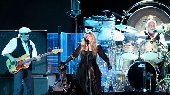 Mehrere Musiker stehen auf einer Bühne und geben ein Konzert.