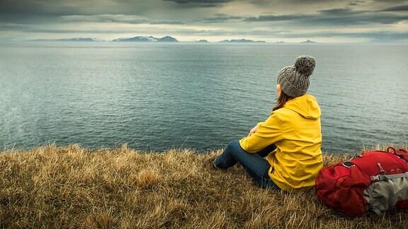 Eine junge Frau in gelber Jacke und Mütze sitzt auf einer Klippe und sieht aufs Meer, neben ihr liegt ein Rucksack