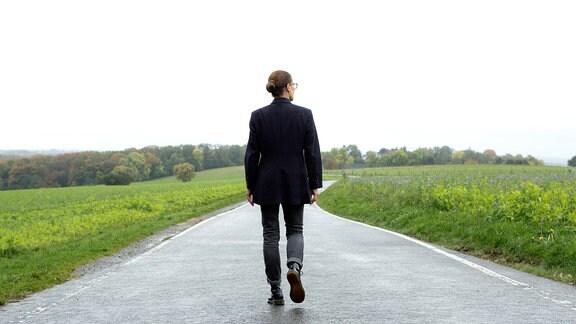 Eine Frau spaziert allein über eine Landstraße.