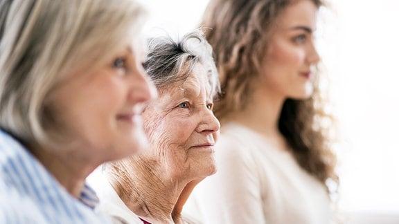 Drei Frauen stehen in einer Reihe nebeneinander.