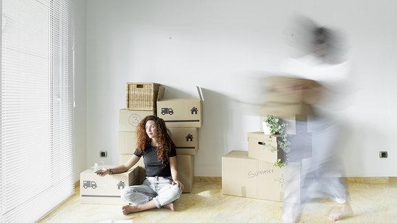 Eine junge Frait auf dem Boden einer Wohnung voller Umzugskartons