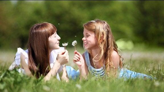 Zwei Mädchen liegen auf der Wiese und pusten Löwenzahnblüten