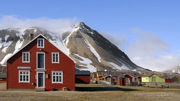 Bunte Holzhäuser vor einem Berggipfel