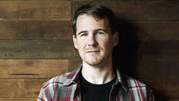 Ein junger Mann mit dunklem Shirt und kariertem Hemd lehnt entspannt an einer Holzwand und schaut leicht lächelnd in die Kamera.