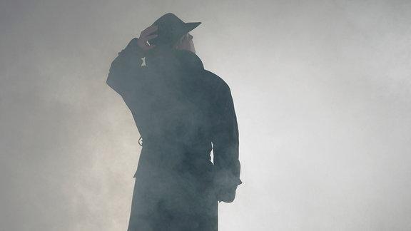 Eine Frau im Trenchcoat steht im Nebel