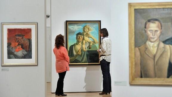 Zwei Frauen betrachten in der Orangerie von Gera das Gemälde -Selbstbildnis mit Jan- (M) von Otto Dix