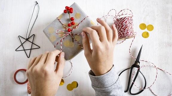 Kinderhände verpacken ein Weihnachtsgeschenk