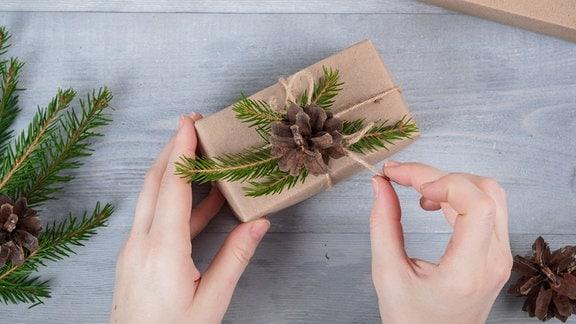 Geschenk in Packpapier mit Tannenzweigdeko