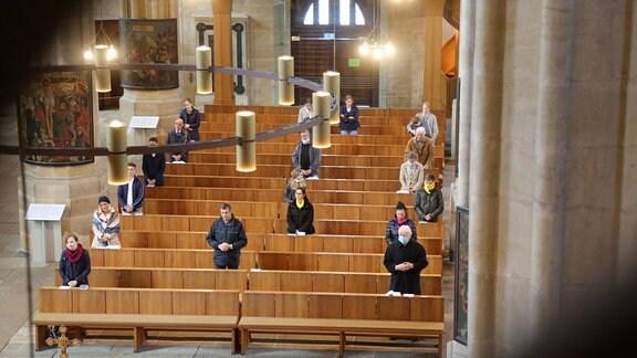 Menschen stehen 2020 mit Abstand in einer Kirche.