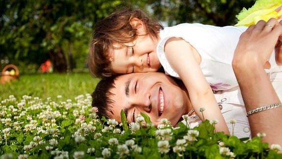 Ein Vater liegt mit seiner Tochter glücklich lachend auf einer Blumenwiese.