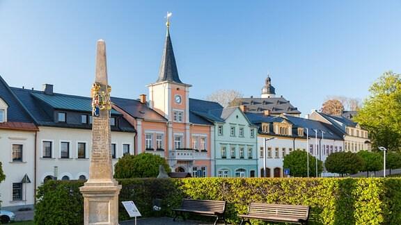 Markt mit Postmeilensäule und Rathaus, im HIntergrund das Schloss
