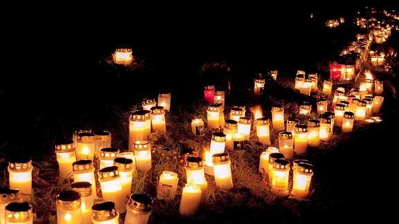 Leuchtende Grablichter auf einem Friedhof