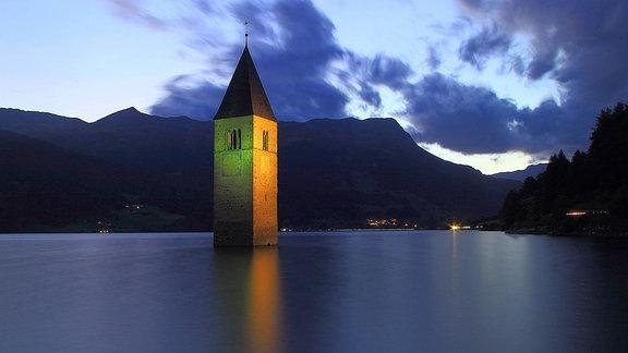 Ein Turm in einem See in Dunkelheit beleuchtet