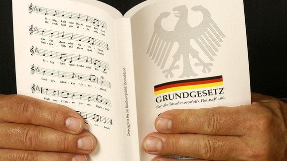 Jemand hält das Grundgesetz der Bundesrepublik Deutschland