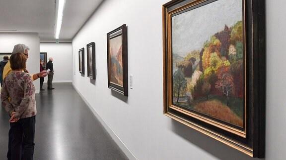 """Besucher in der Dauerausstellung der Kunstsammlungen Chemnitz – Museum Gunzenhauser, vorn das Gemälde """"Frühlingslandschaft mit blühenden Bäumen am Untersee"""" (1944) von Otto Dix"""