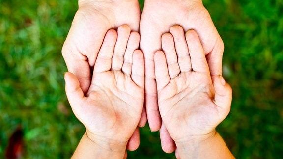 Hände liegen aufeinander