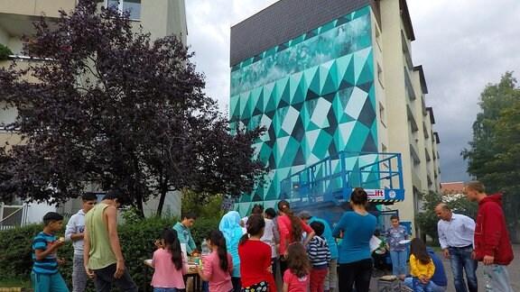 Die von der Freiraumgalerie gestaltete Fassade in der Wolfgang-Borchert-Straße in Halle-Neustadt wird eröfnet.