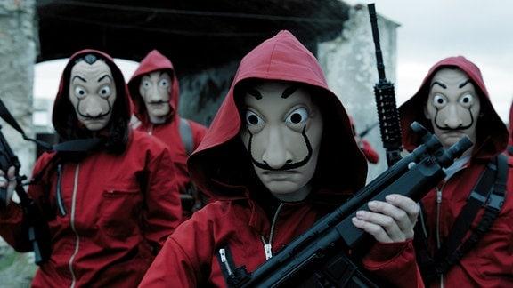 Vier Maskierte halten Waffen