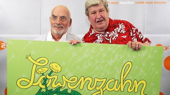 Peter Lustig und Helmut Krauss  halten ein Löwenzahn-Schild.