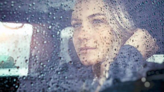 Eine Frau sitzt im Auto, die Scheiben nass vom Regen.