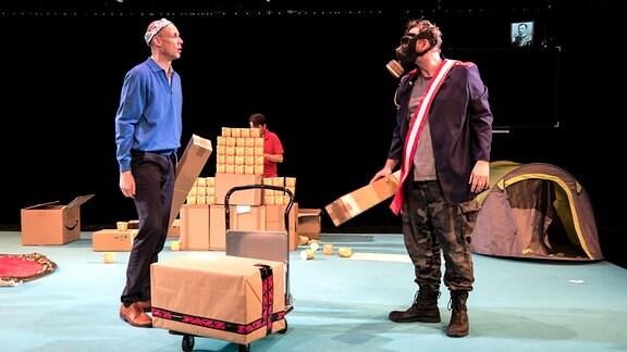 Ein Mann mit einer Alu-Krone spricht mit einem anderen, der eine Gasmaske trägt