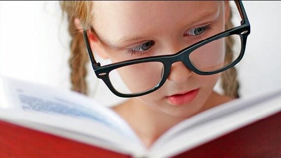 Ein Mädchen mit einer großen Brille ließt in einem Buch