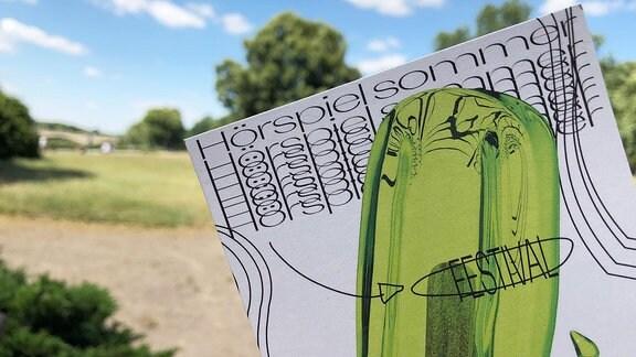 Ein Flyer mit grünem Eis und der Aufschrift Hörspielsommer Festival. Im Hintergrund eine Parklandschaft.