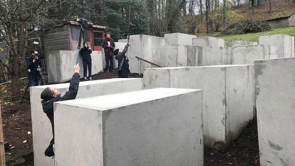 AktivistInnen des Zentrums für Politische Schönheit und das von ihnen gebaute Mahnmal vor Björn Höckes Haus.