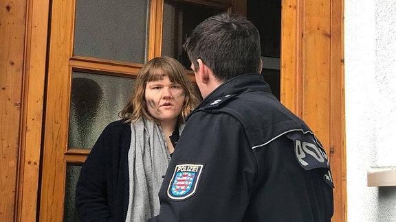 Eine Frau an der Haustür und eine Polizist.