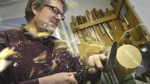 Ein Holzspielzeugmachermeister an der Drechselbank