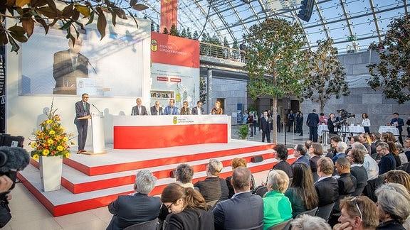 Auf einer Bühne sitzen Menschen hinter einem Podium. Publikum schaut zu. Ein Mann steht an einem Rednerpult.