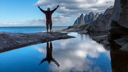 ein junger Mann breitet vor herrlicher Landschaft aus Freiheitsgefühl seine Arme aus.