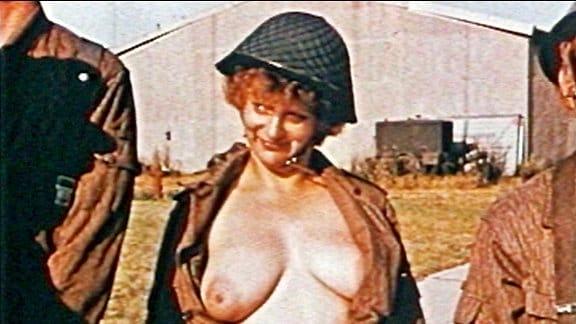 Eine obenrum nackte Frau in einer Soldatenuniform