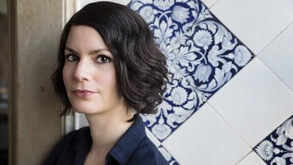 Autorin Isabelle Lehn posiert für ein Photo und schaut in die Kamera.