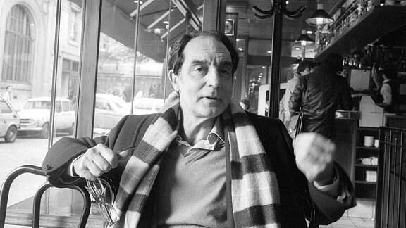 Der Schriftsteller Italo Calvino sitzt in einem Cafe und erzählt etwas.