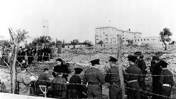 Britische Truppen überprüfen Bewohner vor einer Räumung in Jerusalem. Im Hintergrund rechts steht das ''King David Hotel'' und das YMCA gebäude (links).