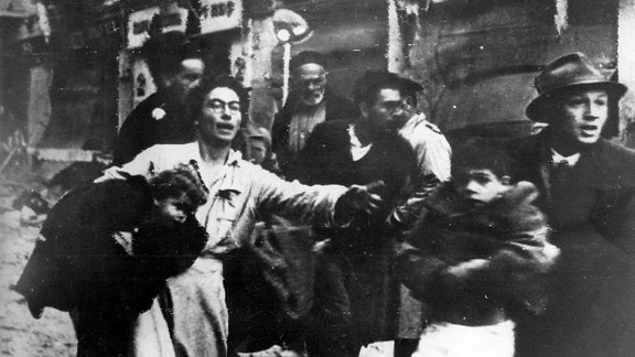 Eine von Entsetzen geplagte Familie mit Kindern, die vor der Explosion in der Ben-Yehuda-Straße in Jerusalem im Februar 1948 flohen.