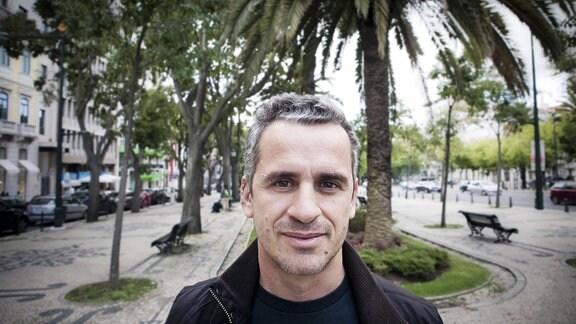 Schriftsteller José Luís Peixoto schaut lächelnd in die Kamera, im Hintergrund ein Boulevard mit Palmen.
