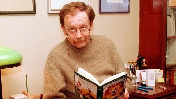 Kabarettist Jürgen Hart liest ein Buch in seinem Büro in seiner Wohnung in Berlin. 2000