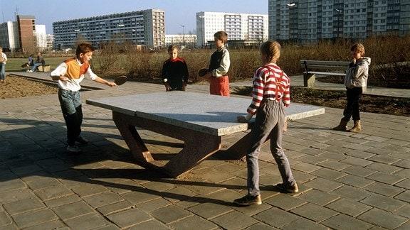 Kinder spielen am 21.02.1990 Tischtennis auf einem Spielplatz in einer Plattenbausiedlung in Halle-Neustadt.