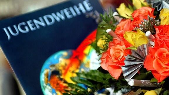 Eine Jugendweihe-Urkunde liegt 2016 neben einen Blumenstrauß.