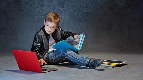 Ein Junge mit einem Buch und einem Laptop