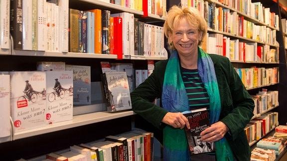 Jutta Voigt lehnt auf dem 20. Literaturfestival des Vereins Erfurter Herbstlese an einem Bücherregal.
