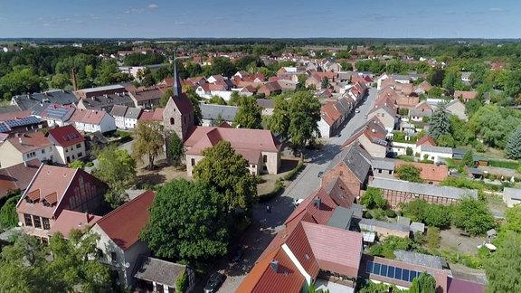 Luftbildaufnahme eines Dorfes, die Dorfkirche sticht markant hervor.