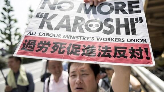 Arbeiter hält Plakat bei Protest hoch